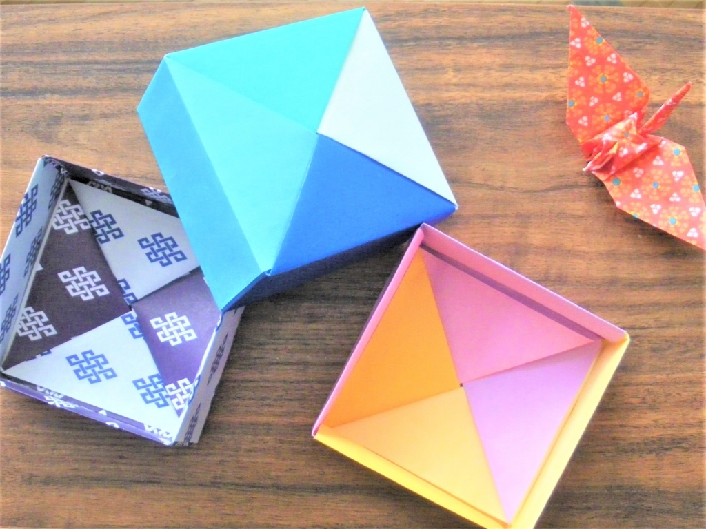 折り紙で作った四角形の小物入れと折り鶴の画像