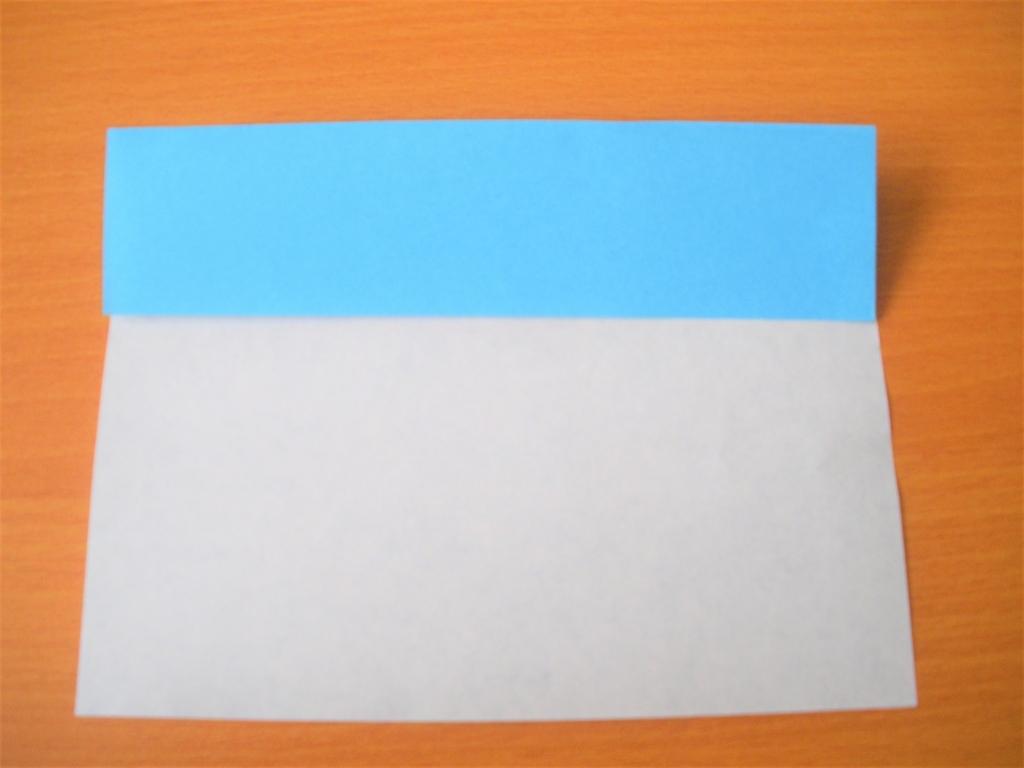 折り紙の上の部分を中心に合わせて折り返す画像