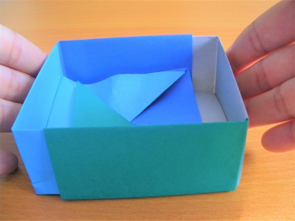 両側を手で押して箱を完成させる画像