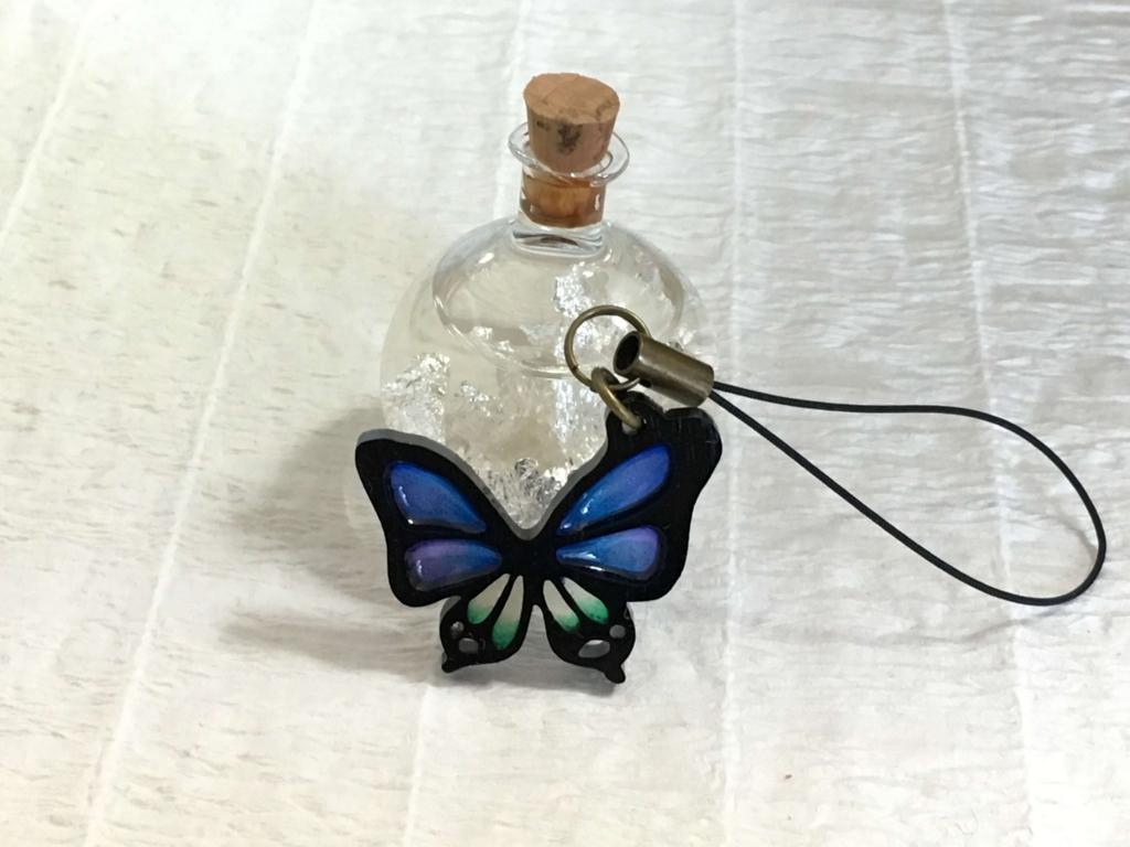 蝶のキーホルダーと銀箔の入ったアルコールボトル