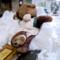 雪で作られた椅子に座る熊のぬいぐるみ