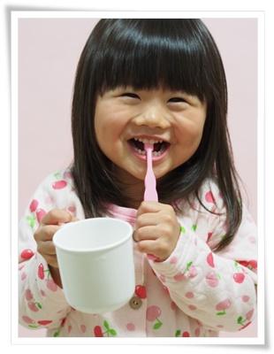 笑顔で歯磨きする女の子