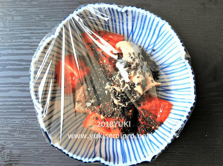 さば水煮缶とトマトと黒ゴマ入り耐熱皿にラップをかけた画像