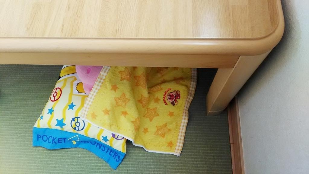 テーブルの下に、子供用枕とピンク色のぬいぐるみがチラリと見える写真。