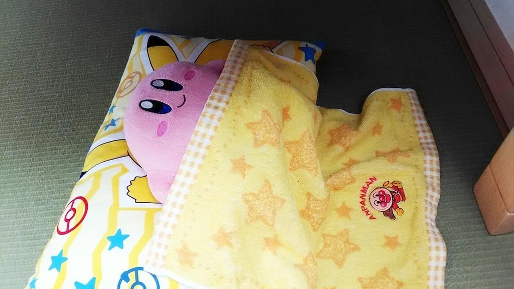 テーブルの下に置いてある子供用枕に、ぬいぐるみのカービィが小さなお布団をかけて寝ている写真。