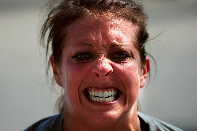 強張った表情の女性 画像