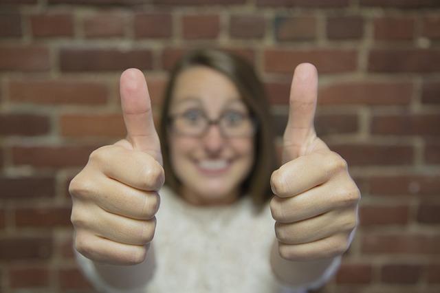 女性が親指を立てて笑顔