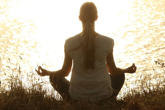 湖のほとりで瞑想する女性