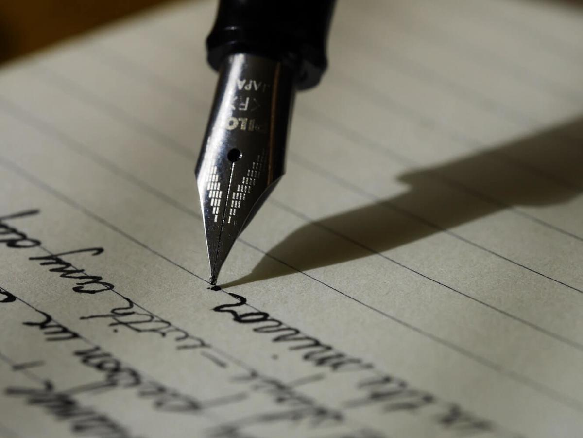 ペンでノートに文字を描く