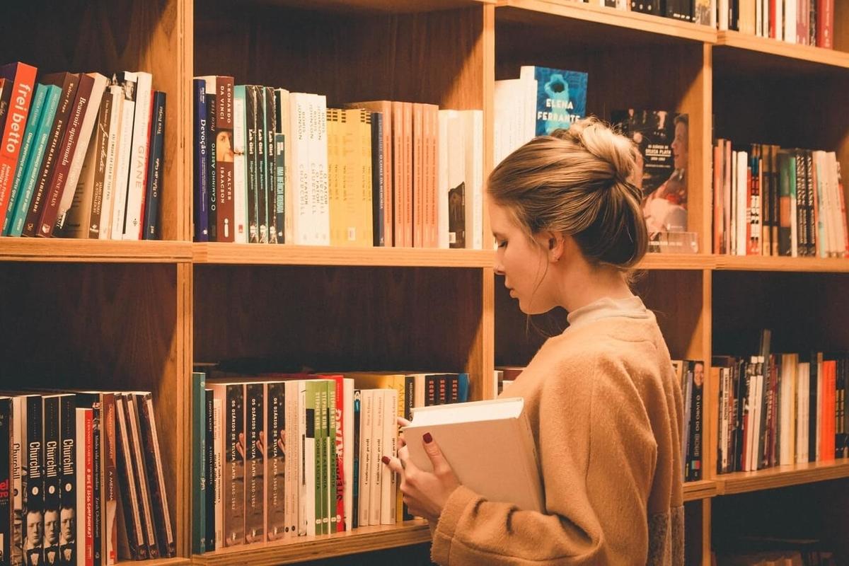 図書館で女性が本を選んでいる