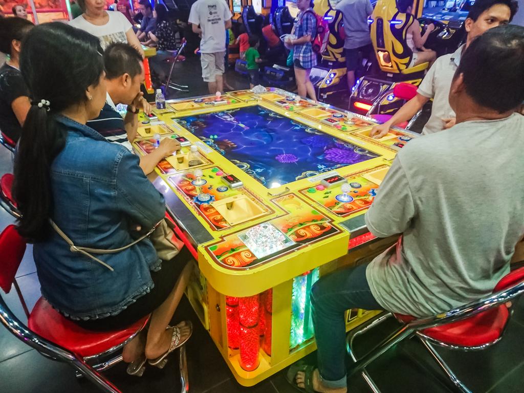 ベトナムのゲーセン。魚撃ちゲームを囲むどうしようもない大人たち。