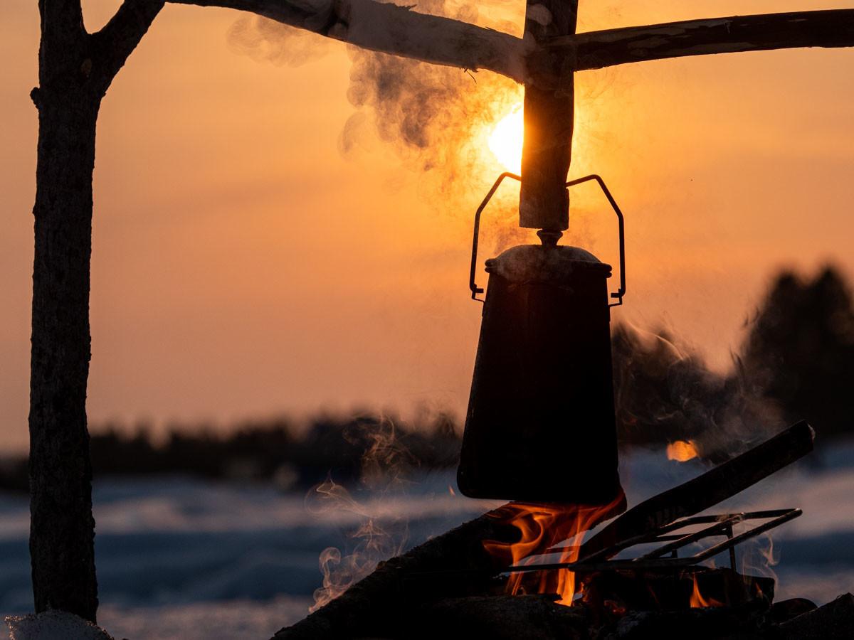 夕陽で逆光のアウトドア用ケトル