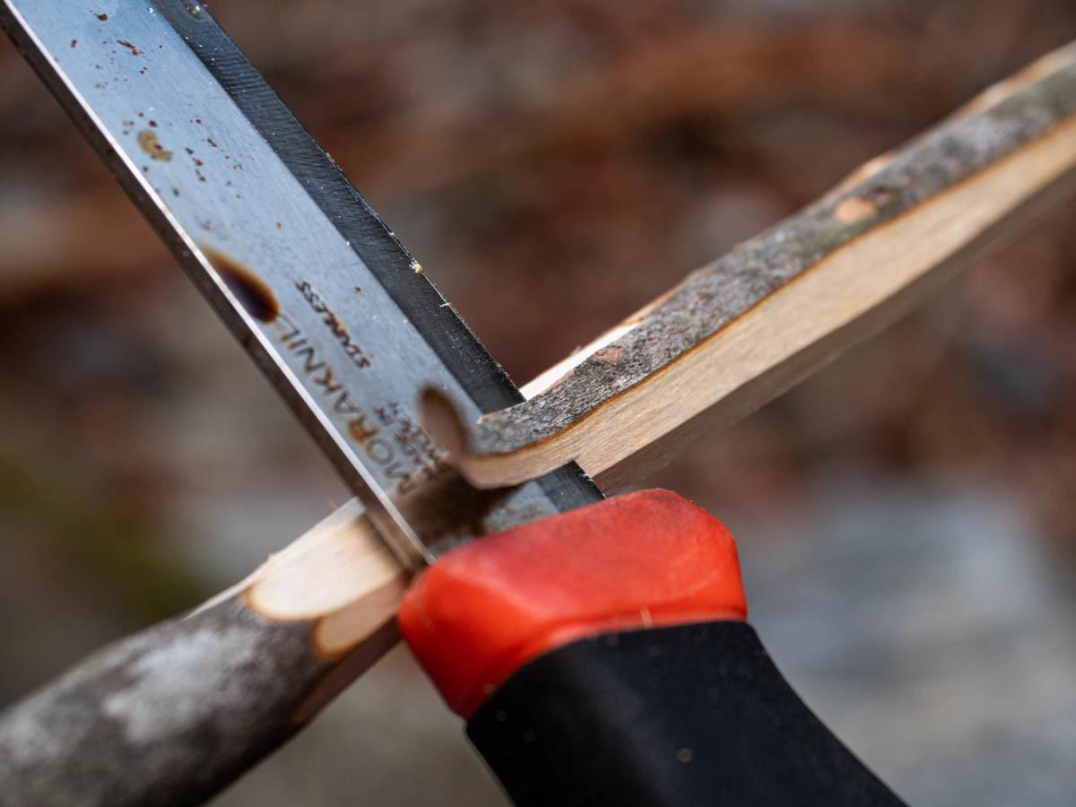 木の皮をナイフで剥ぐ