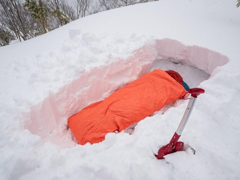 雪の中で寝袋で寝ている姿