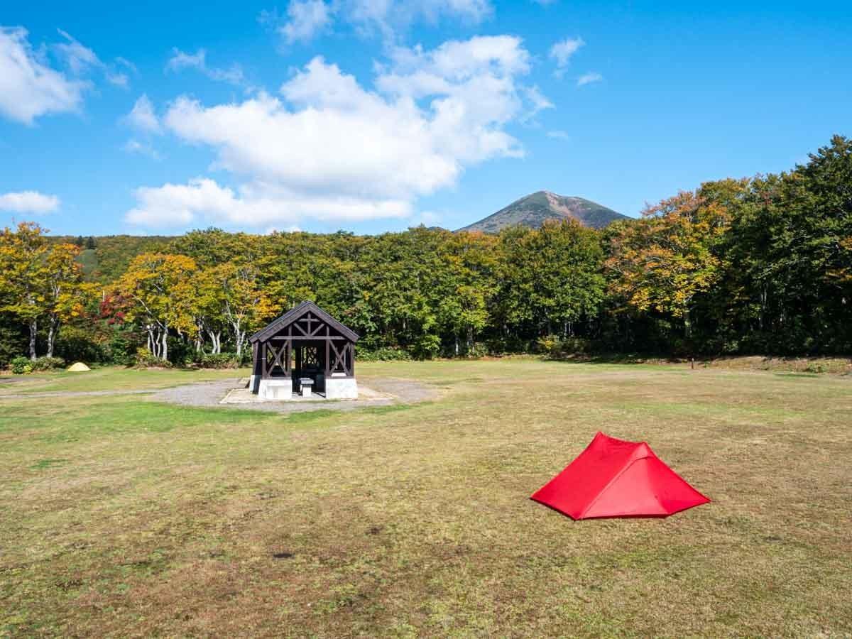 青空のキャンプ場にテントを張る