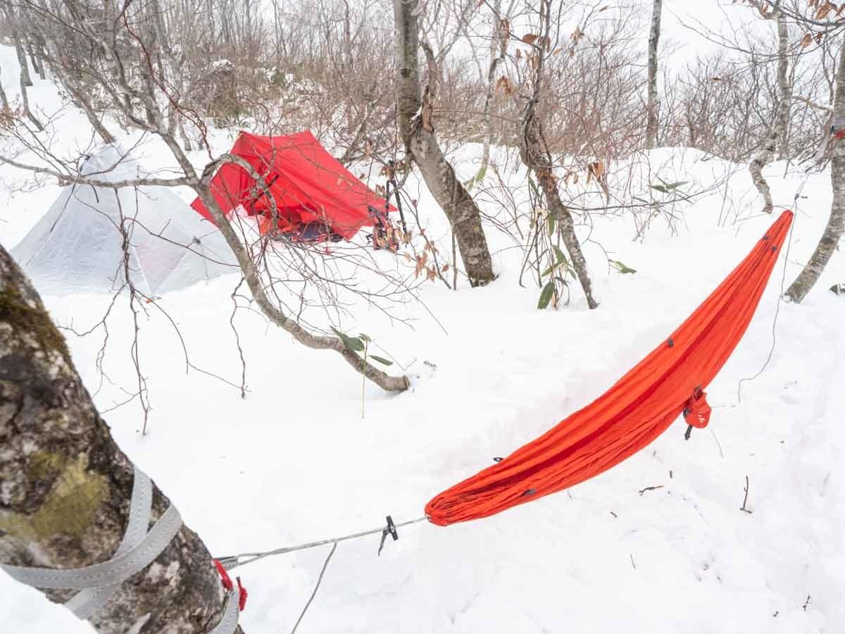 雪上にハンモックとテントを設営