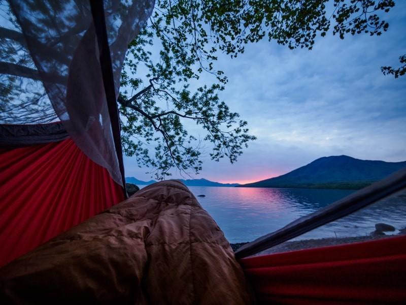 ハンモックの上で寝袋に入ったまま見る日の出前の湖