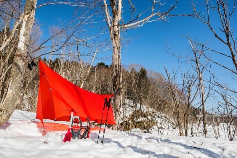 雪上にスノーシューとタープを張る