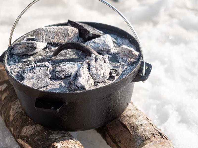 ダッチオーブンに炭を載せて調理